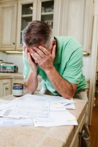 Mature man with head in hands over table of household bills